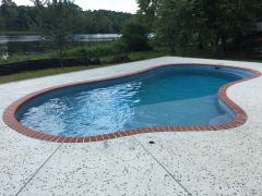 Freeform fiberglass pool with concrete deck