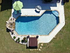 Lazy L Vinyl Swimming Pool with Stone Coping_ Hot Tub Enclosure_ Real Stone Waterfall