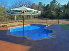 Small Lazy L Vinyl Swimming Pool with Umbrella_ Stained Decorative Concrete Decking